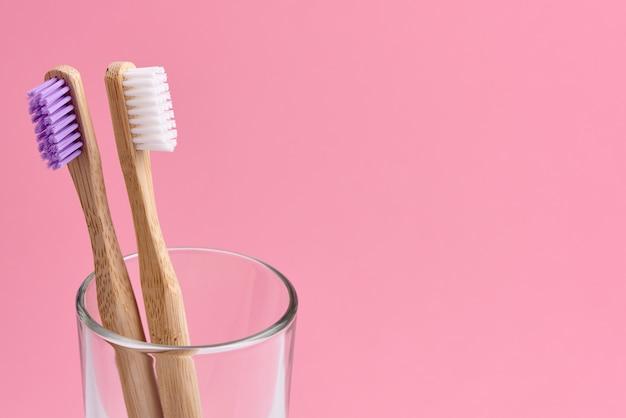Spazzolini da denti di bambù in vetro su sfondo rosa