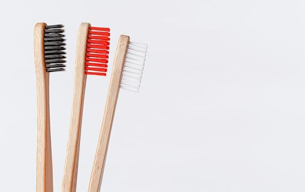 Spazzolini da denti di bambù rossi, bianchi e neri su bianco