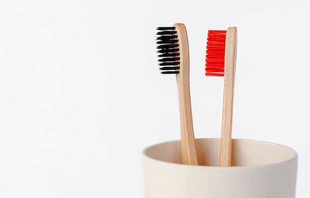 Spazzolini da denti di bambù rossi e neri in tazza di eco. copia spazio, vicino.