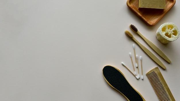 Spazzolini da denti di bambù, sapone naturale su un piatto di legno, luffa da bagno e altri prodotti per la cura del corpo ecologici su uno sfondo di carta beige. concetto di rifiuti zero. vista dall'alto. copia spazio.