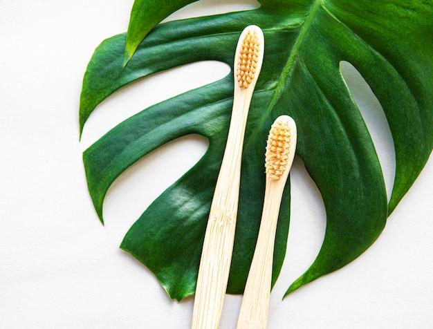 Spazzolini da denti di bambù su superficie bianca