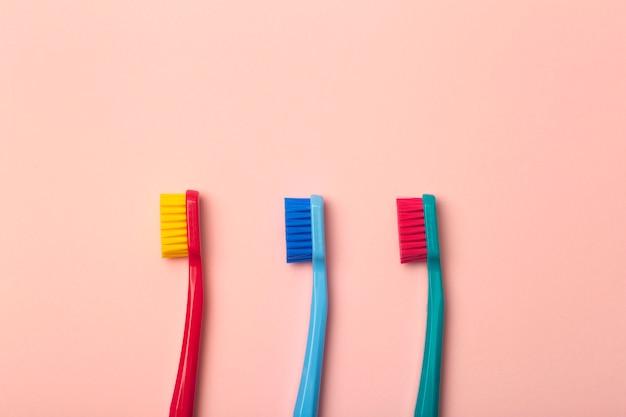 Spazzolini da denti di diversi colori sul rosa