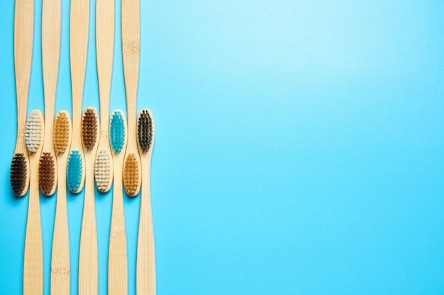 Spazzolini da denti di legno su una vista superiore del fondo blu con lo spazio della copia.