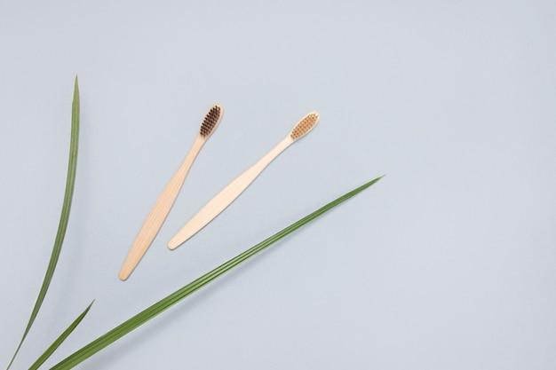 Spazzolini da denti ecologici di bambù su uno sfondo grigio, vista dall'alto. zero sprechi. concetto di salute. igiene alternativa del prodotto orale.