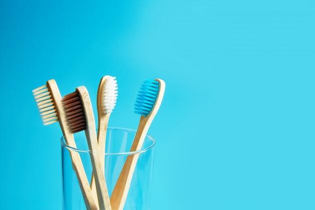 Spazzolini da denti in legno con una tazza di vetro su uno sfondo blu con spazio di copia.
