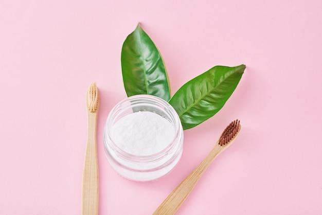 Spazzolini da denti in legno di bambù con bicarbonato di sodio in barattolo di vetro e foglie verdi su una superficie rosa. denti salute e mantenere il concetto di bocca