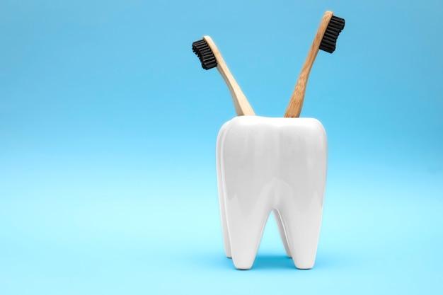 Spazzolini da denti in legno di bambù nel supporto a forma di dente concetto di assistenza sanitaria dentale. copia spazio. beni ecologici, protezione dell'ambiente