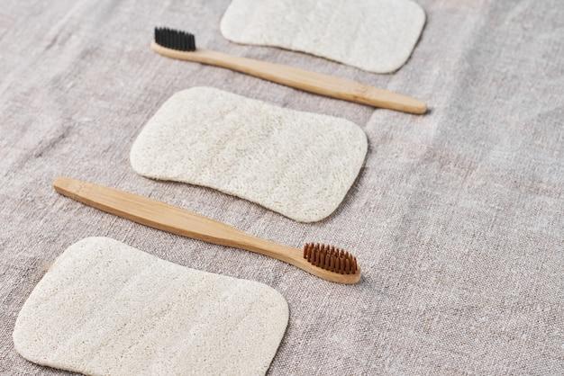 Spazzolini da denti in legno e lavamani naturali su tela grigia, vista dall'alto