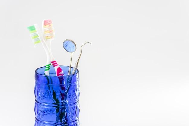 Spazzolini da denti in un set di vetro e cure odontoiatriche isolato su sfondo bianco.