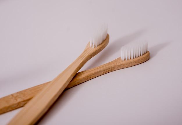 Spazzolini da denti, pezzuole per lavare, tazze e piatti di bambù sul tavolo bianco in cucina