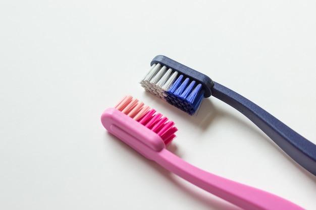 Spazzolini da denti rosa e blu su backgound bianco