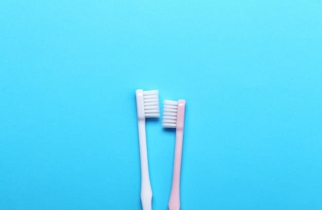 Spazzolini da denti rosa e grigi sulla parete blu.