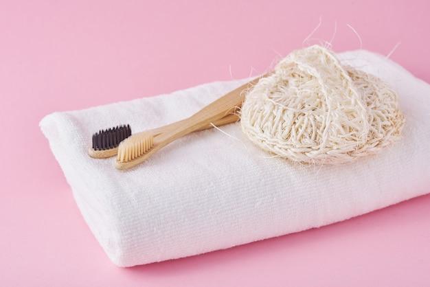 Spazzolini da denti, spongle e asciugamano bianchi amichevoli di bambù di legno di eco su un rosa.