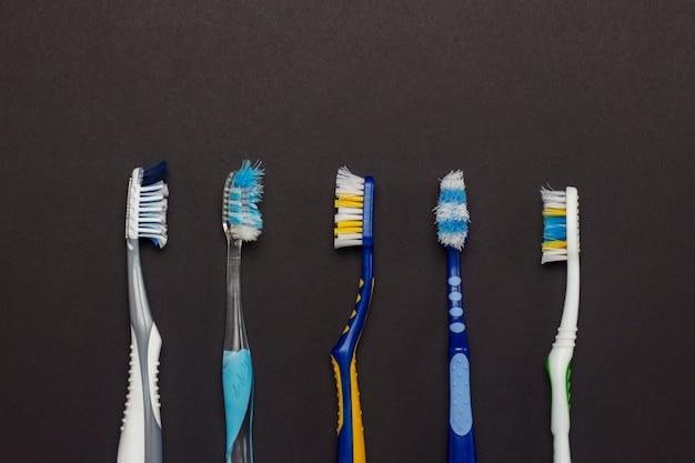 Spazzolini da denti usati di diversi colori su sfondo nero. concetto di igiene orale, igiene personale, stomatologia. vista piana, vista dall'alto.