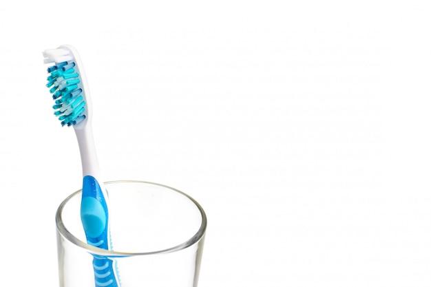 Spazzolino colorato in un bicchiere isolato su uno sfondo bianco