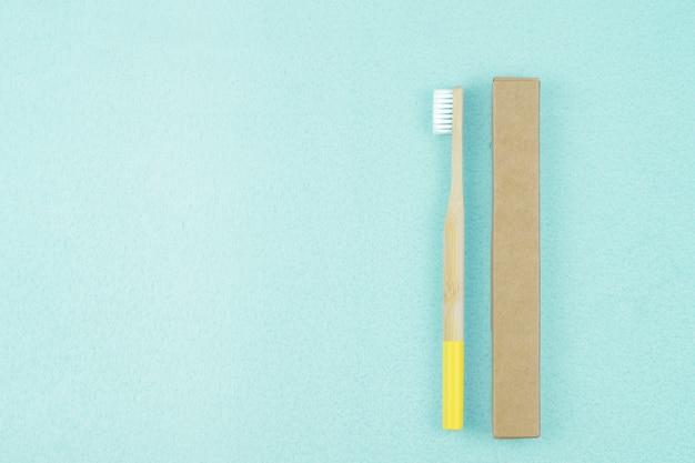 Spazzolino da denti di bambù ecologico nell'imballaggio di carta su un fondo blu