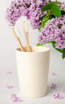 Spazzolino da denti di bambù in tazza di eco con i fiori lilla su bianco