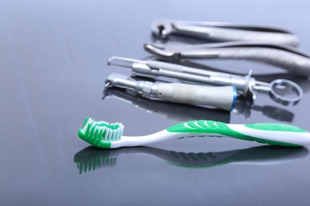 Spazzolino da denti di cure odontoiatriche con gli strumenti del dentista sul fondo dello specchio.