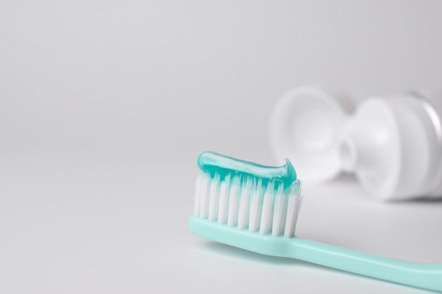 Spazzolino da denti e dentifricio su sfondo sfocato
