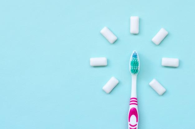 Spazzolino da denti e gomme da masticare giacciono su un blu pastello