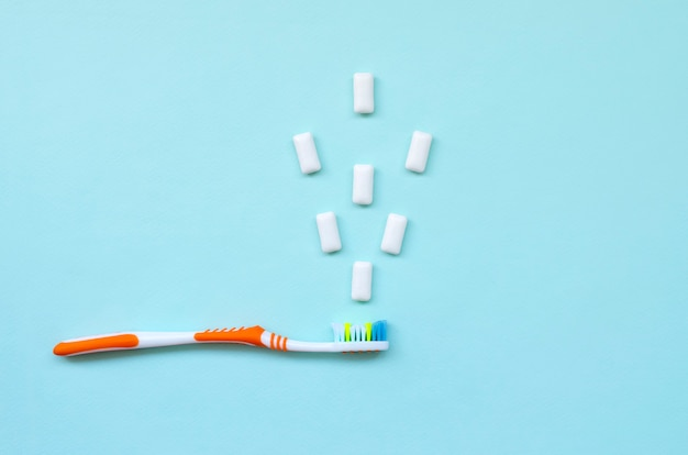 Spazzolino da denti e gomme da masticare si trovano su uno sfondo blu pastello. t
