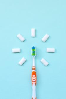 Spazzolino da denti e gomme da masticare si trovano su uno sfondo blu pastello