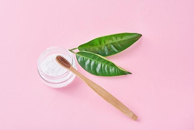 Spazzolino da denti in legno di bambù con bicarbonato di sodio in barattolo di vetro e foglie verdi su sfondo rosa.