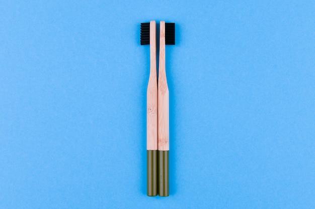 Spazzolino da denti in legno su sfondo blu. chiuda sullo spazzolino da denti di legno su un fondo blu. pennello ecologico.