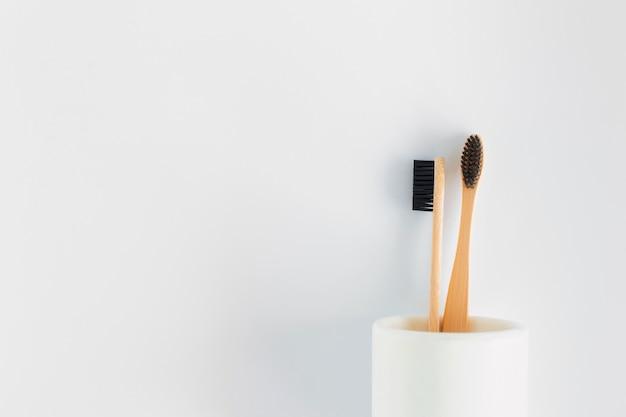 Spazzolino da denti naturale del bambù di eco nel supporto su fondo bianco