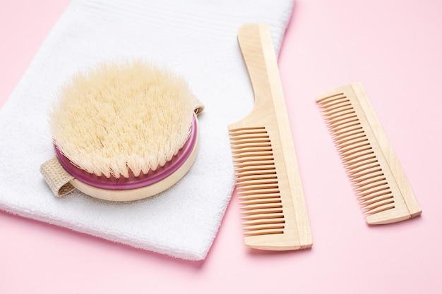 Spazzolino da denti, pettine e spazzola di legno di eco per il massaggio a secco sul rosa