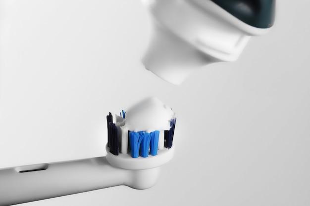 Spazzolino elettrico e dentifricio isolati sulla parete leggera con lo spazio della copia per testo.