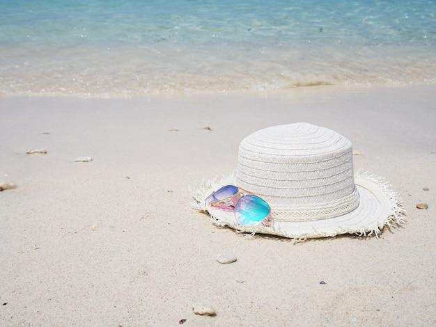 Specchi gli occhiali da sole e cappello bianco sul fondo della spiaggia di sabbia