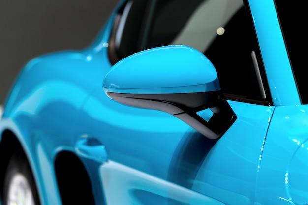 Specchietto laterale blu con auto moderna blu.