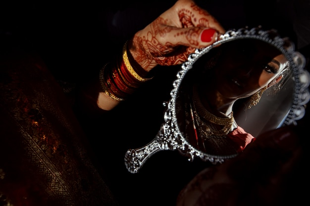 Specchio d'argento nelle mani della sposa indù con tatuaggi all'henné