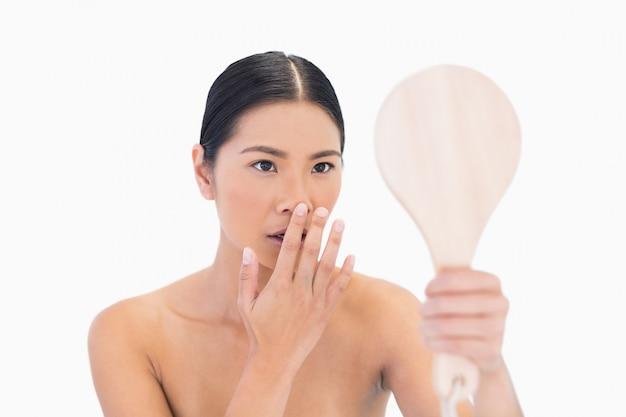 Specchio di modello di modello dai capelli scuro naturale che tocca il suo naso