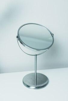 Specchio per il trucco su un tavolo bianco.