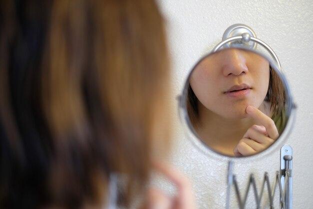 Specchio riflesso di una donna che tocca il suo viso