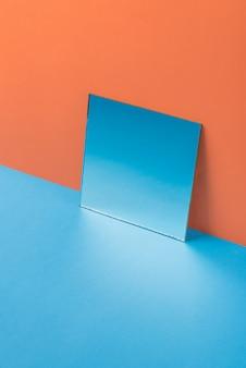 Specchio sulla tavola blu isolata sull'arancia