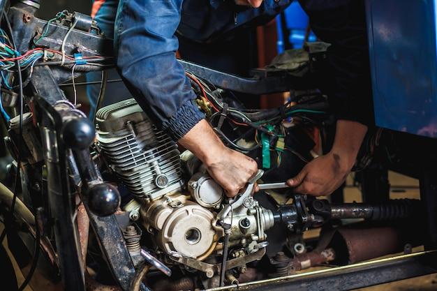 Specialista in tute che lavorano con biciclette motorizzate nel garage di riparazione.