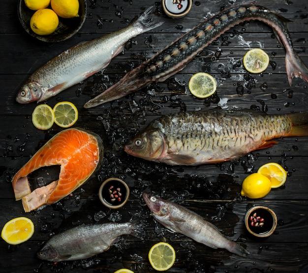 Specie di pesce crudo su un tavolo di legno nero con fette di limone intorno.