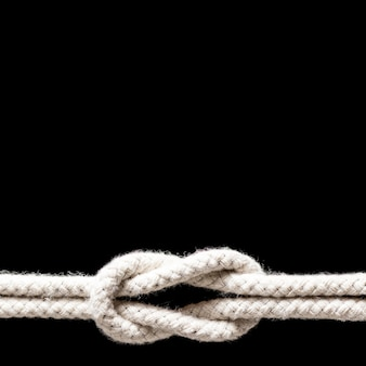 Spedica il nodo bianco delle corde isolato su fondo nero