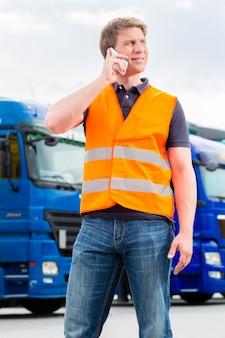 Spedizioniere davanti a camion su un deposito