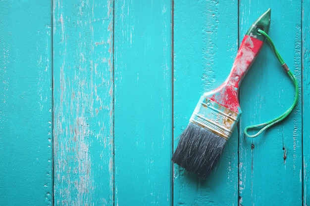 Spennellare con vernice blu chiaro su fondo in legno chiaro vernice di legno.
