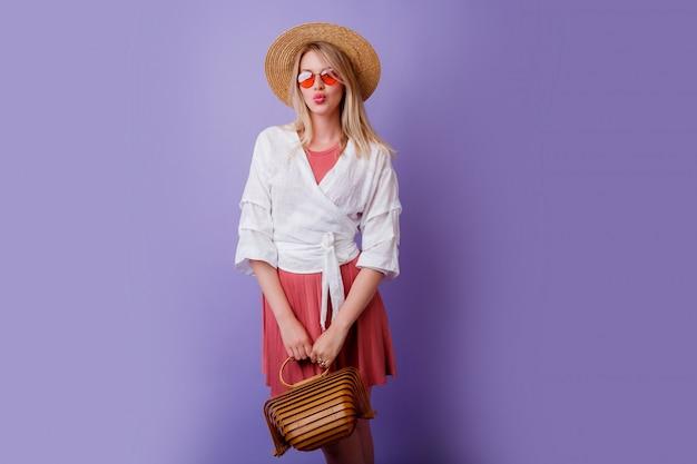 Spensierata donna bruna in abito rosa alla moda e cappello di paglia tenendo borsa di bambù su viola.