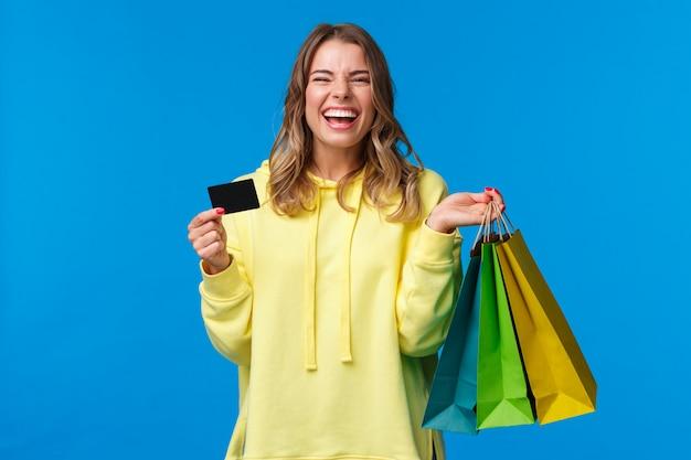Spensierata emotiva, sorridente felice bella ragazza bionda che usa la carta di credito per sprecare un po 'di soldi nel centro commerciale, tenere le borse della spesa, comprare regali o regali, regalarsi una giornata, ridere con gioia