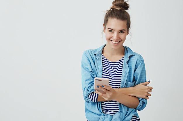 Spensierato tenero attraente giovane donna fiduciosa capelli pettinati hairbun sorridente, ridendo divertendosi tenendo smartphone cercando felice ghignando scherzando intorno