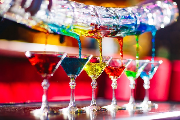 Spettacolo di barman. il barista versa cocktail alcolici.