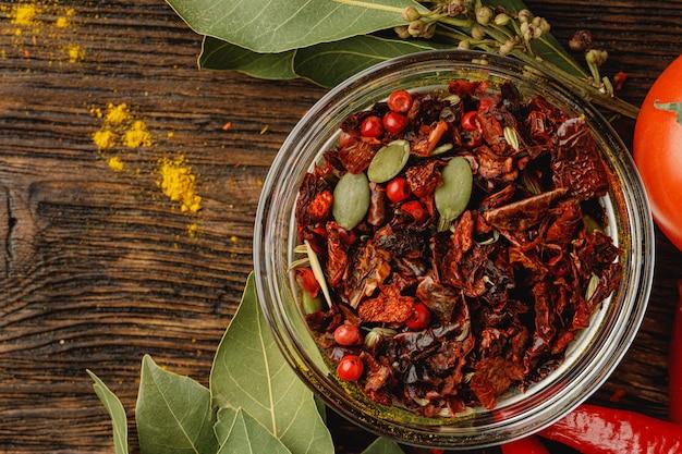 Spezia rossa del peperoncino rosso in ciotola di vetro con le erbe sulla tavola scura