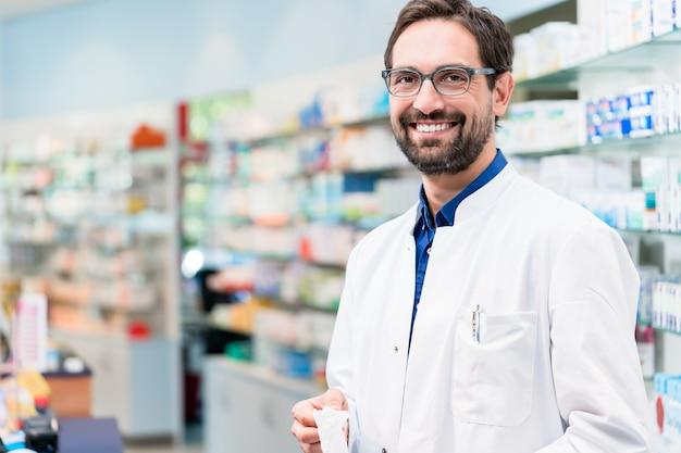 Speziale in farmacia in piedi a scaffale con farmaci