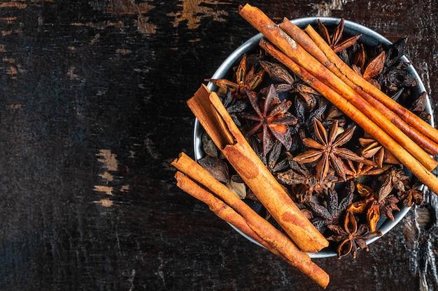 Spezie alla cannella e stelle di anice in una ciotola sul tavolo
